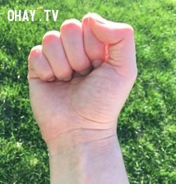 Ngón tay cái đặt trên ngón tay trỏ khi nắm tay